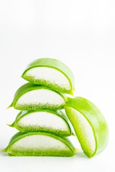 Close-up natural organic aloe vera plant sliced for homemade cosmetic liquid against white background.