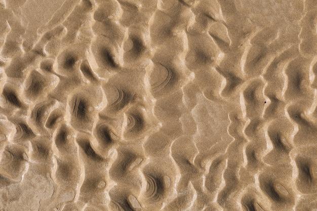 夏の自然ビーチ砂ウェットテクスチャを閉じます。セレクティブフォーカス。砂の壁、壁紙