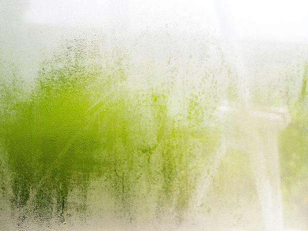 Крупным планом природа капли воды текстуры на стекле с размытым зеленым фоном. влажность воздуха, вызывающая пар на стекле.