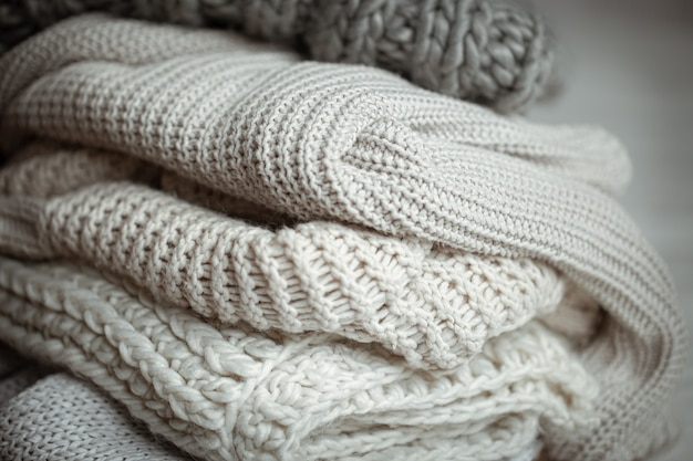 Close up of neatly folded knitted items of pastel color.