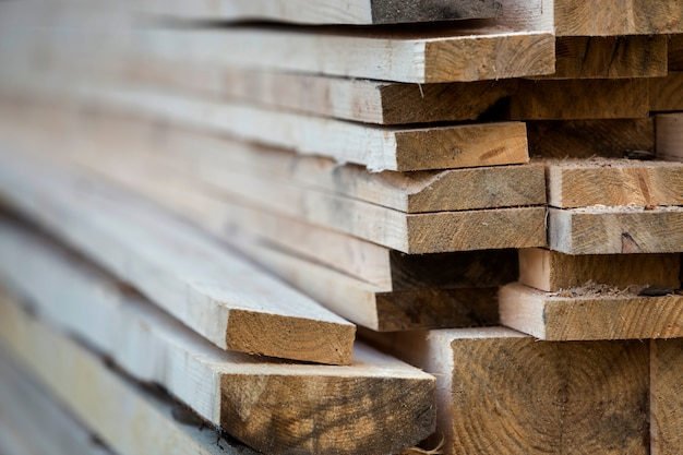 Close-up of neatly piled stack of natural brown uneven rough wooden boards lit by bright sun. industrial timber for carpentry, building, repairing and furniture, lumber material for construction.