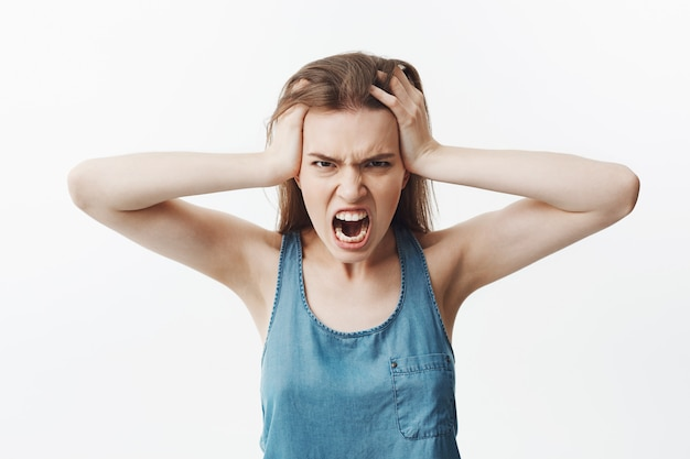 Close up of negative young european student girl with long dark hair in blue shirt head with hands,  with mad and angry face expression, screaming loudly
