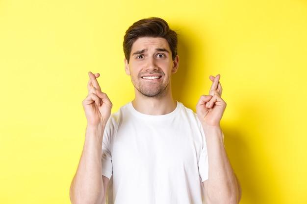 Primo piano dell'uomo nervoso che esprime desiderio, tenendo le dita incrociate e mordendosi il labbro preoccupato, in piedi su sfondo giallo.