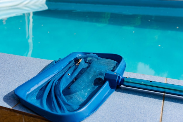 Close up of net cleaner on pool tile