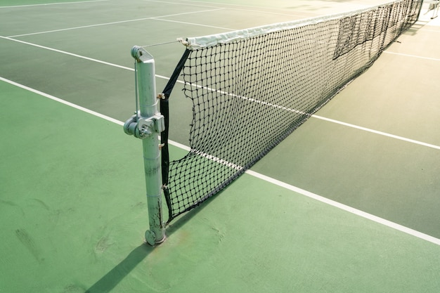 Close up of a net on a hard tennis court on a sunny day.