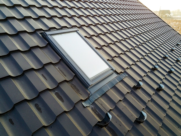Close-up of new attic plastic window installed in shingled house roof. professionally done building and construction work, roofing and installation concept.