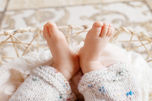 Close up  of new born baby feet on knitted plaid in a wattled basket. soft newborn baby fingersl. baby. cozy. family