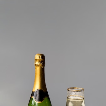 Close-up of new champagne bottle and glass on grey wall