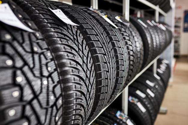Крупным планом новые шины в автосервисе, новые зимние шины с современным изолированным протектором. выборочный фокус. фон стека шин. зимний сезон, без людей