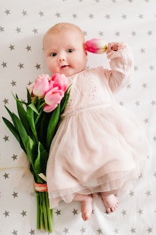 Close-up of newborn baby girl hand holding a bouquet of flowers pink tulips. new life, love and holiday concept. mother's day. flat lay. top view.