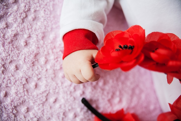 Close-up of newborn baby hand holding flowers