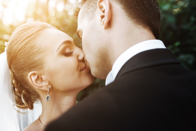 Close-up of newlyweds in love kissing