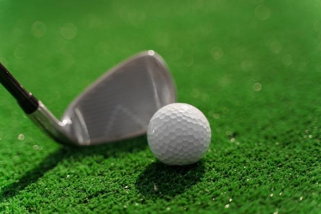 Крупный план ниблик и белый мяч для гольфа на зеленой траве