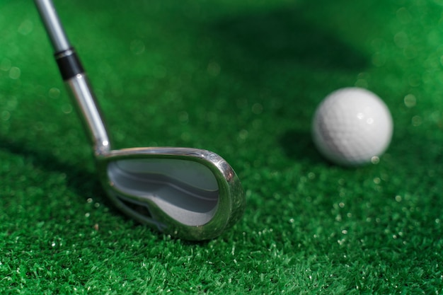 Close-up niblick and white ball for golf on the green grass