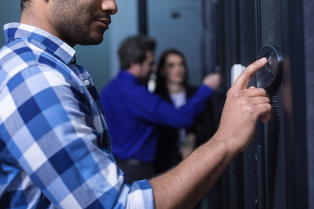Close up of a nice handsome young man looking at the control panel and pressing the button while entering the code