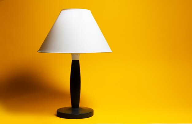 Close-up of night lamp with white shade and black tripod on background of orange color.