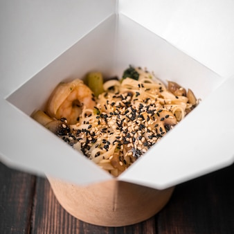 Close-up of noodles in box with sesame seeds and chopsticks
