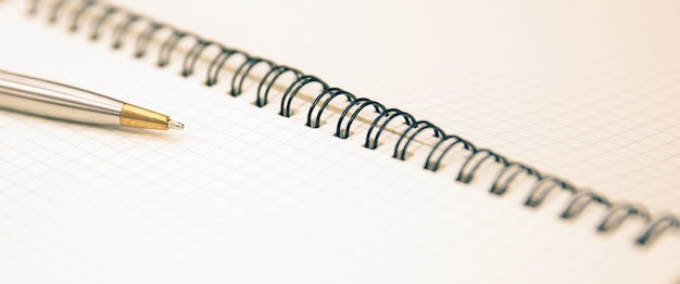 Close-up note book with a pen on the table.