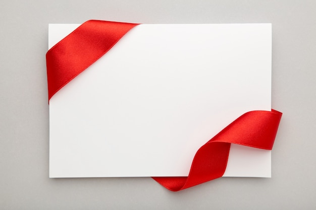 Close up of a note card with ribbon bow on grey background. top view.