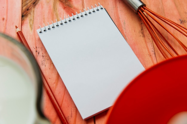 Close-up of notepad; pencil and whisk on wooden plank