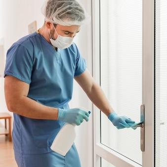 ドアハンドルを消毒するクローズアップの看護師
