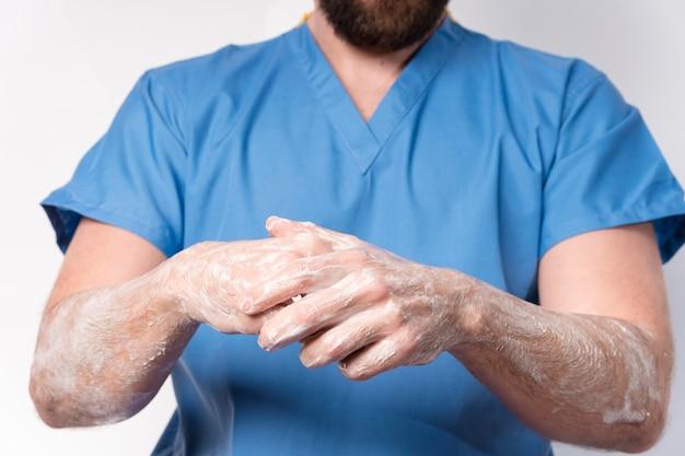 Mani disinfettanti dell'infermiera del primo piano