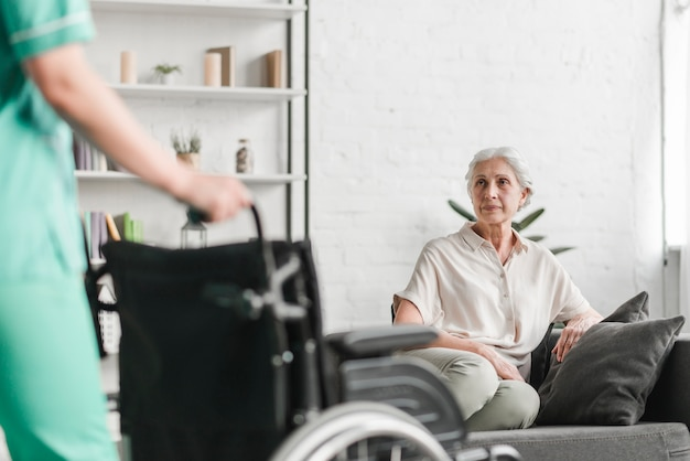 Close-up of nurse holding wheelchair in front of senior female patient
