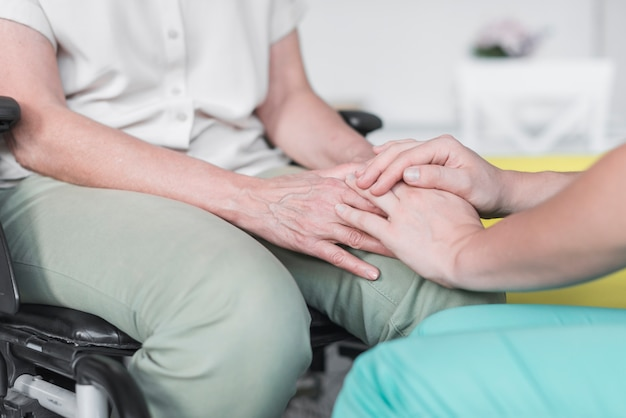 Close-up of nurse and patient holding each other's hand