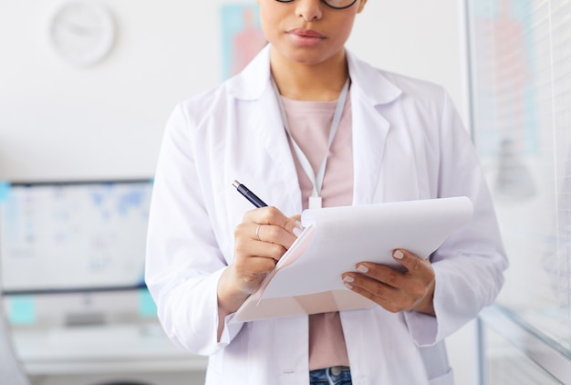 Close-up of nurse in white coat prescribing a medicine while working at hospital