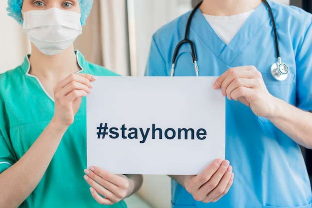 Close-up nurses with stay home message