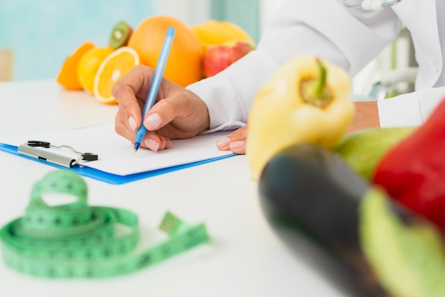 Close-up nutritionist writing prescription
