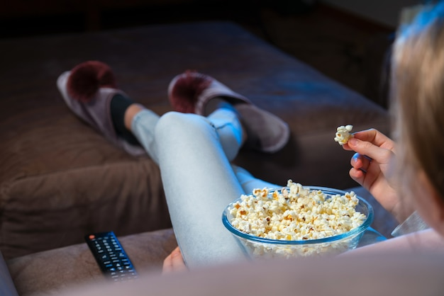 Close up o f hand waking popcorn from a bowl while watching tv. person sitting in comfortable couch and watching home cinema in the dark.