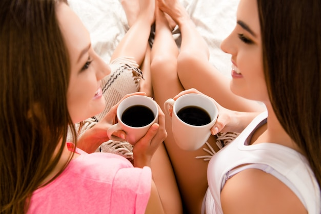 Close up o two pretty happy girls drinking coffee in morning