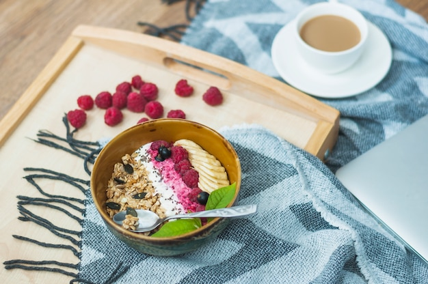 Close-up of oatmeal bowl with raspberries on wooden tray
