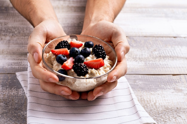 Close up oatmeal porridge with berries in glass bowl in men's hands