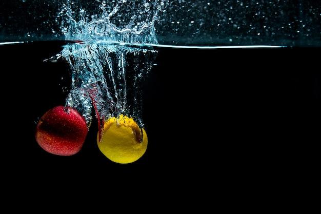 閉じる。オブジェクトの撮影。水にレモンとリンゴ。