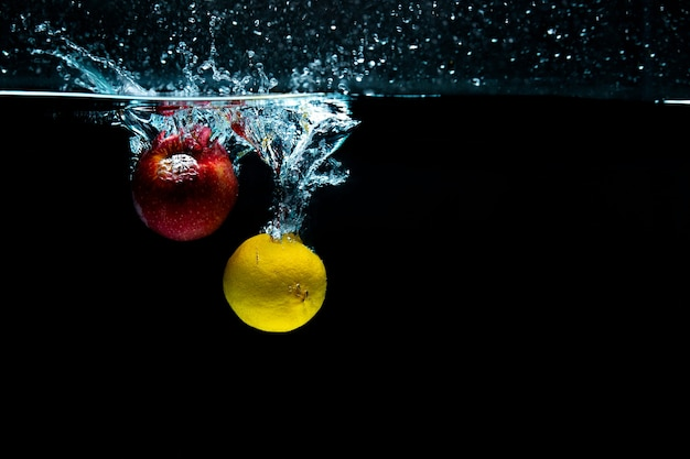 Close-up. object shooting. apple with lemon in water.