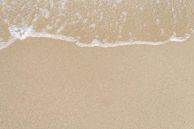 모래 해변에서 바다 물결 거품을 닫습니다. 휴가 휴가와 자연스러운 느낌에 대한 배경.
