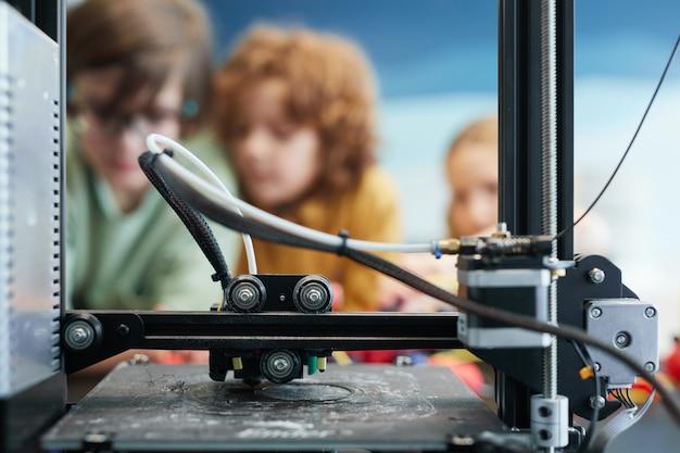Крупный план 3d-принтера, делающего пластиковые модели во время урока инженерии и робототехники в школе с детьми в фоновом режиме, копией пространства