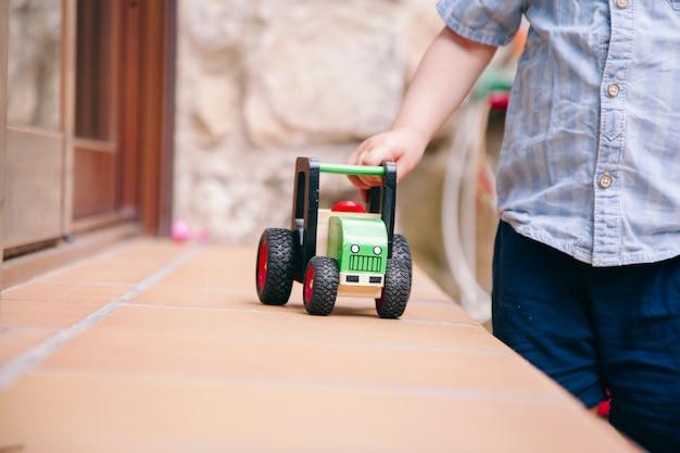 Закройте вверх ребёнка играя с традиционной игрушкой дома.