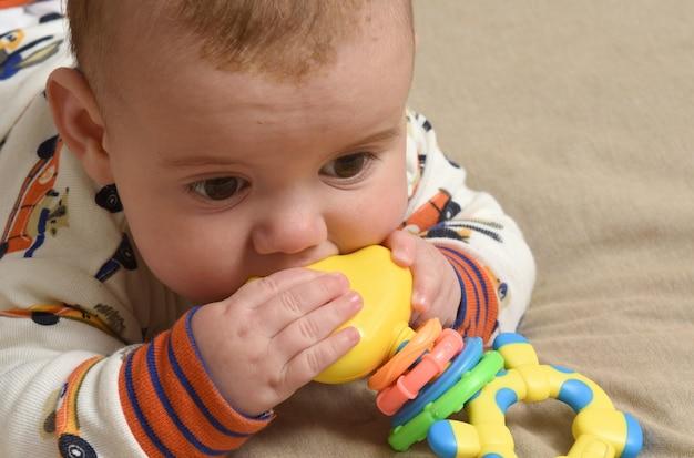 おもちゃで遊んでいるベッドに横たわっている赤ちゃんのクローズアップ、
