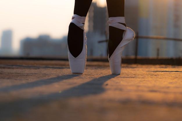 개성의 일몰 개념 동안 도시 장소에서 신발에 발레 댄서의 발을 닫습니다