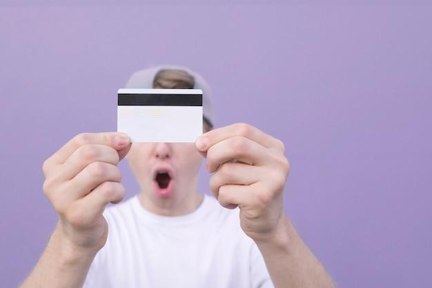 パステルパープルの背景に感情的な男の手に銀行カードのクローズアップ