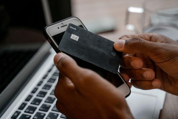 銀行のプラスチックカードのクローズアップ。ノートパソコンとスマートフォンを使用して、職場の背景に黒いクレジットカードまたは預金を手に入れます。