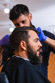 이발소에서 남자의 머리를 절단하는 이발사의 근접-이발소에서 수염을 가진 젊은 남자의 프로필.