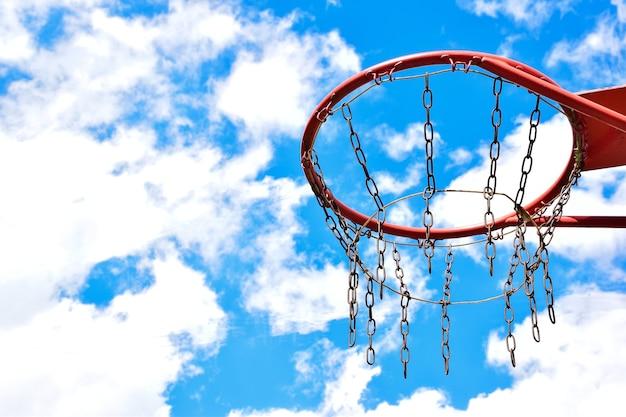 흰 구름이 있는 밝은 푸른 하늘을 배경으로 오른쪽에 있는 농구 골대의 클로즈업. 왼쪽에는 텍스트를 삽입할 수 있는 빈 공간이 있습니다.