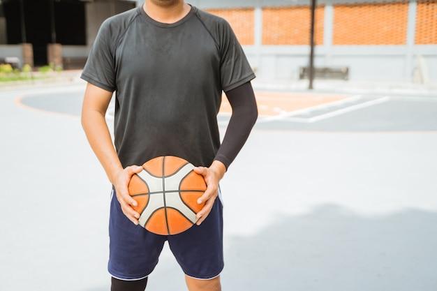 バスケットボールを持っているバスケットボール選手の手のクローズアップ