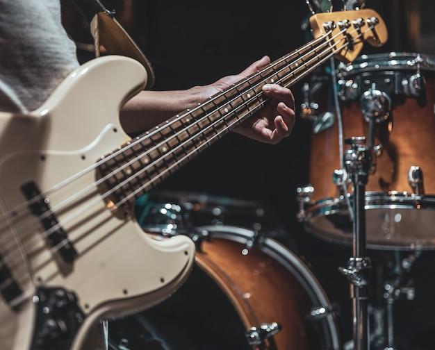 연주 과정에서 음악가의 손에 있는 베이스 기타의 클로즈업.