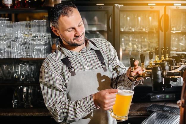 Крупный план бородатого бармена, наполняющего кружку светлого пива. барная стойка в пабе.