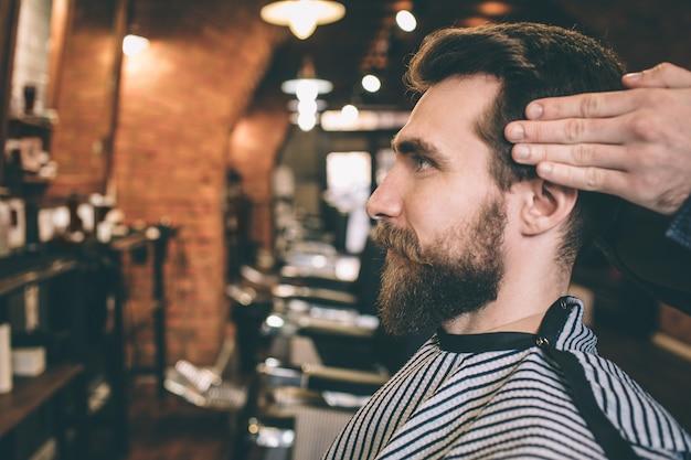 Крупным планом бородатый парень. его парикмахер стрижет и моделирует волосы.